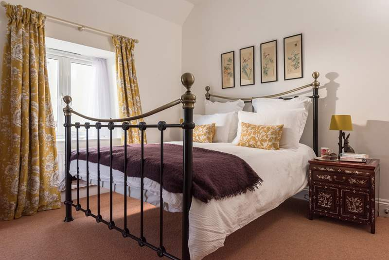 The lovely double bedroom with large metal bed.
