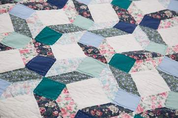A pretty patchwork quilt on the bed.