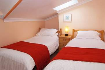 The twin bedroom has a sloped ceiling and is comfortably furnished.