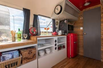 The kitchen is very well-equipped and features a funky red Smeg fridge.