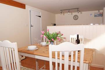 The open plan living space has a lovely kitchen tucked into one corner and a little farmhouse dining-table.