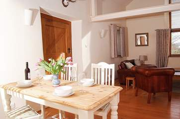 The open plan living area has lovely wooden floors and has cleverly divided living, dining and kitchen areas.