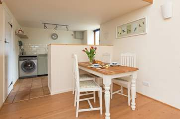 There is a little farmhouse dining table and the kitchen area is beyond.