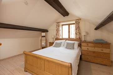 The mezzanine area is the bedroom, with this lovely king-size sleigh bed.