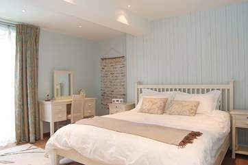 Tranquil colours in Bedroom 3 and doors out to the balcony.