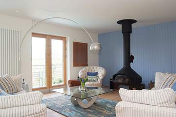 The sofas in the open plan living-room are set around a ceiling-hung Focus wood fire.