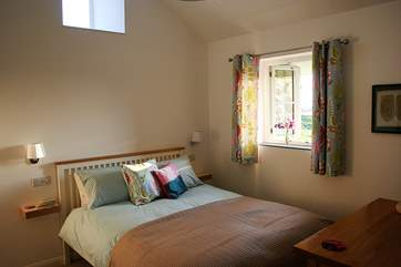 The beautifully furnished bedroom with those wonderful countryside views and en suite shower-room.