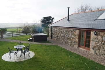 The garden has views across the countryside to the sea beyond and doors opening into the living-room.