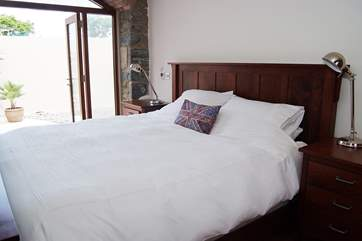 The master bedroom (Bedroom 1) has an impressive 6' wooden bed alongside other furniture made by Amish craftsmen in the USA.