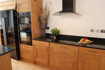 There is a double oven alongside the large American-style fridge/freezer.