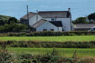 Stargazy Skies is the single-storey cottage in the middle of the picture with two windows. The backdrop of the sea is stunning.