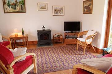 The open plan sitting-area is complete with a wood-burner effect electric stove.