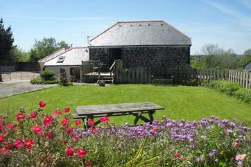The view of the cottage from the end of the garden with parking to the left.