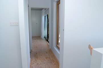 The ground floor hallway with the stairs on the right of the picture and the twin bedroom at the end.