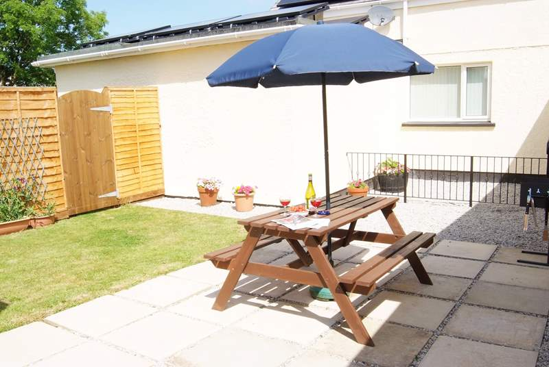 The patio-area and garden bask in sunshine, ideal for a barbecue.