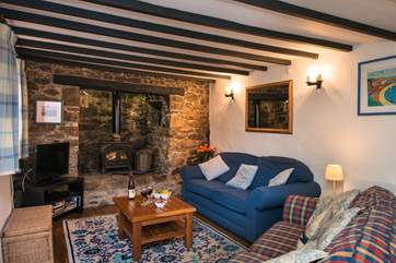 The traditional sitting room is very cosy with its  beamed celing and stone fireplace
