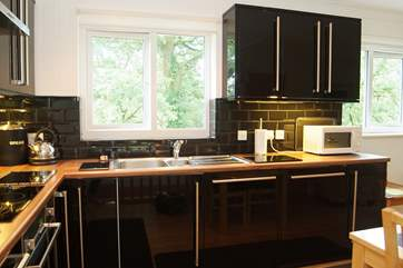 The kitchen-area looks out over shrubs and trees.