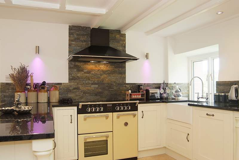 Granite work surfaces, an electric range cooker and colour-changing lights in the kitchen-area.