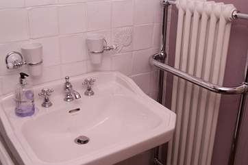 The bathroom in the cottage is gorgeously fitted out with a sink, bath and even radiators.