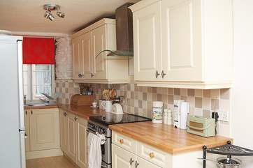 The well-fitted kitchen with a cheery bright red blind at the window.