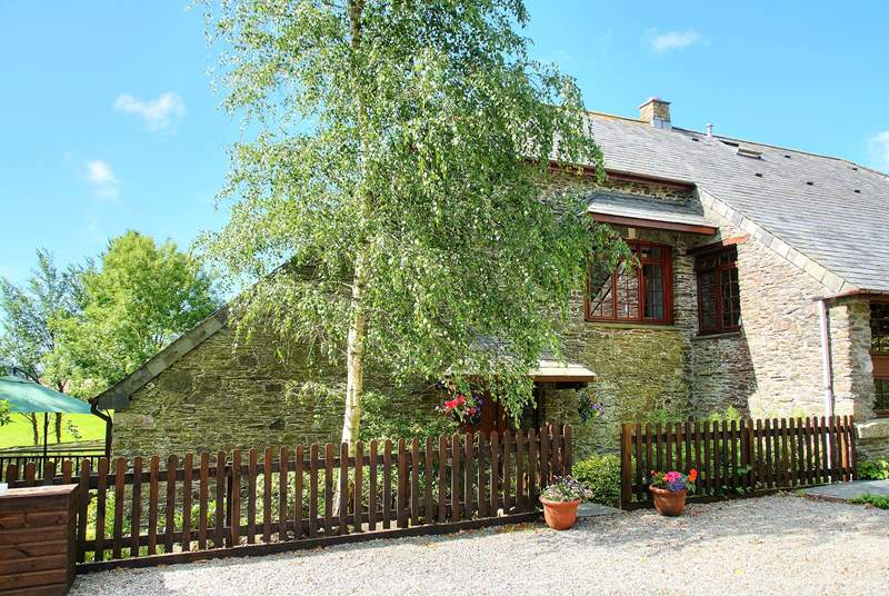 The front of this lovely cottage with the deck and garden to the left.