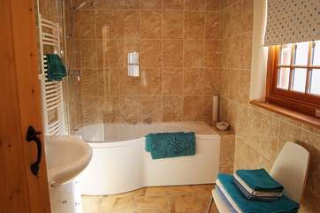 The large family bathroom has a large bath and fitted shower and plenty of room to dry off.