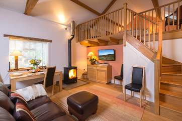 The spacious open plan interior includes a wood-burner and a high beamed ceiling, both adding lots of character to this lovely property.