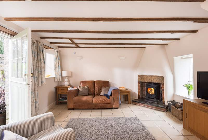 The sitting-room with comfy sofa, chair and the cosy wood-burner.