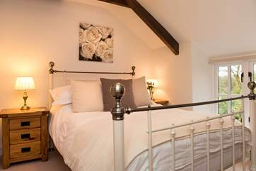 The double bedroom on the first floor has a beautiful bedstead