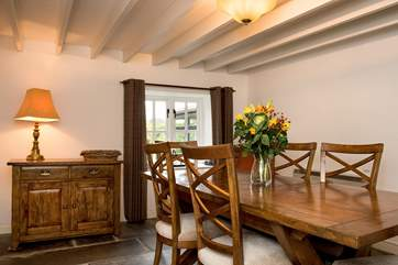 The dining room retains the original features with its beamed ceiling and slate floor
