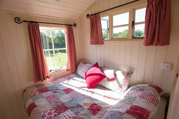 The double bed is positioned to enjoy the lovely views.