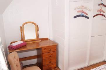 There is a dressing-table and mirror in the single bedroom.