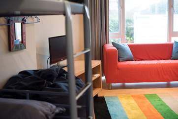 The bunk-bedroom equipped with a television and sofas for the kids to enjoy.