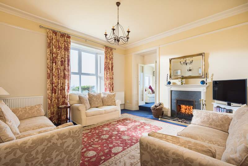 The sitting-room with comfy sofas around the fire.