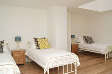 Bedroom 2 is spacious and furnished with three single beds.