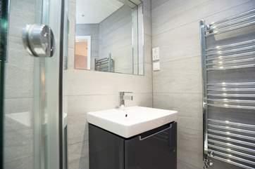 A wall-hung wash-basin sits below the de-mist mirror.