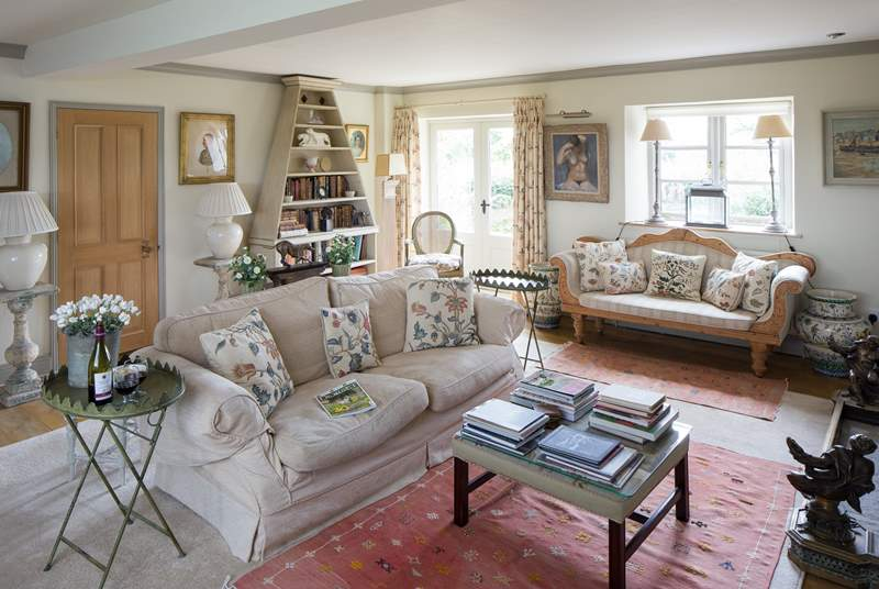 The elegant drawing room has French windows that open out onto the garden at the back of the farmhouse.
