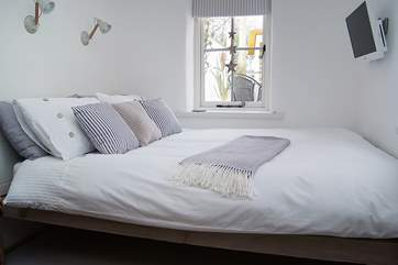 The bed with a TV at the end.