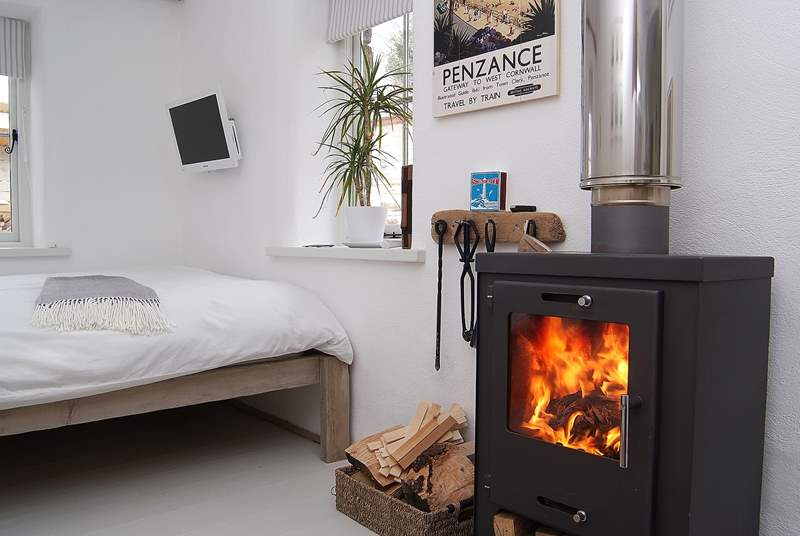 The wood-burner is set next to the comfortable double bed.
