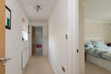 A short corridor links the two bedrooms and the bathroom.