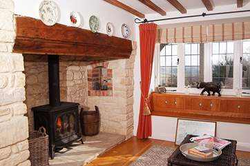 The living-room is so cosy, with a gas-fired wood-burner effect stove and lovely natural wooden floors.