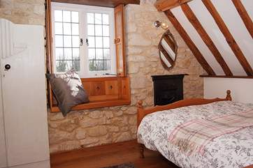 The double bedroom is at the front of the cottage, with wooden floors, a wash-basin - and of course the lovely views.