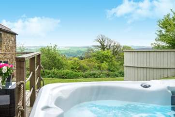 The hot tub is located to the side of the cottage and takes full advantage of the stunning views.