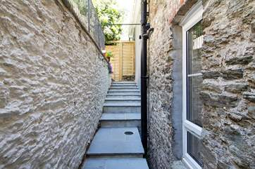 Uneven and different height steps lead from the back door to the terraced garden (take care with children).