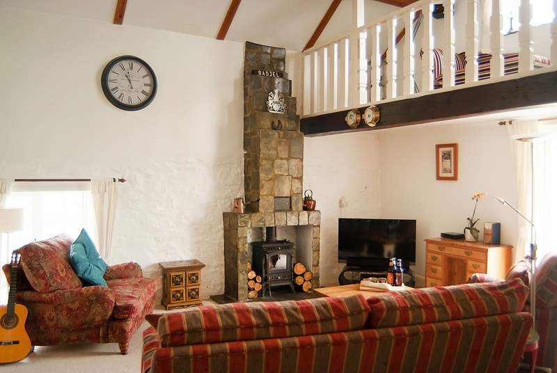 The spacious sitting-room with vaulted ceiling and galleried sitting-area with a view from the balcony across to the estuary.