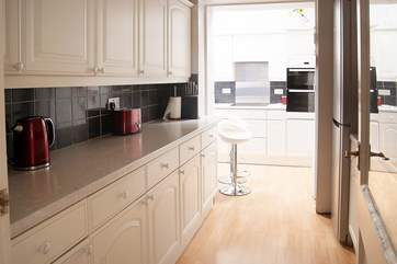 The spacious L-shaped kitchen is fully equipped for the keenest cook.