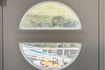 Looking out through the 'porthole' onto the balcony and fishing boats beyond.