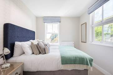 This lovely bedroom has views to the rear terrace and sea glimpses through the little window.