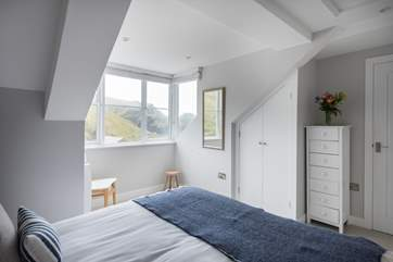 The gorgeous bedroom has wonderful views across the harbour below.