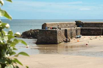The beach is sheltered by a stone breakwater.